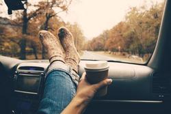 Woman feet in warm socks on car dashboard. Drinking take away coffee on road. Fall trip. Rain drops on windshield. Freedom travel concept. Autumn weekend.