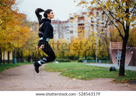 Shutterstock Woman feet jumping, using skipping rope in park. Beautiful brunette sportsgirl doing cardio exercises.