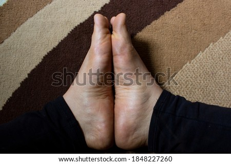 Woman feet lighted by the sun on a carpet