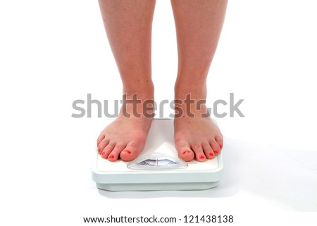 Woman feet on a scale as she checks her weight.