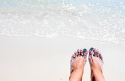 Woman feet on hot sunny beach. Relaxed barefoot tourist by sea. Seaside banner template. Sea water tide on white sand beach. Exotic summer vacation background. Bare feet girl with mermaid nail polish