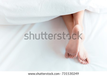 Woman feet on the bed under white blanket. Sleeping and relax concept. Vacation and Holiday theme