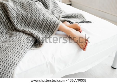 Shutterstock Woman feet under gray blanket sideview. Beautiful young woman feet with red pedicure on the bed. Sleeping woman legs under the gray blanket