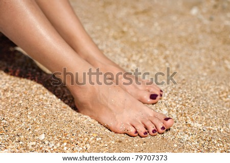 Woman feet with dark pedicure relaxing on the sand