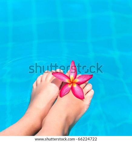 woman feet with flowers in blue water