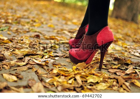 Woman feet  with pink fashion shoes on a late autumn shooting