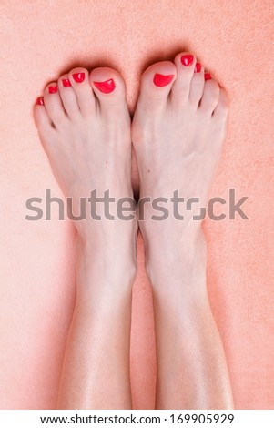 woman feet with red toenails on pink towel