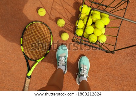 Woman feets, racket and tennis balls on clay court