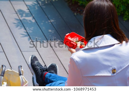 woman female eat lunch in her lunch box in the park #1068971453