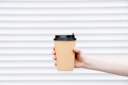 Woman female hand with coffee cup paper latte. Cup in a holder, coffee cup to go takeaway.Top horizontal view