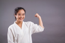 woman fighter portrait; asian woman practicing martial arts, mixed martial arts, MMA, kick boxing, karate studio isolated portrait; girl fighter training concept; 20s young adult asian woman model