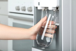 Woman filling glass with water cooler indoors, closeup. Refreshing drink