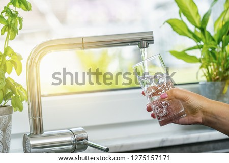 Woman filling glass with water from faucet in kitchen Photo stock ©