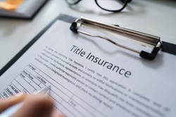 Woman Filling Title Insurance Form Over White Desk