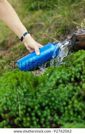 Woman filling water bottle from spring on hiking trip