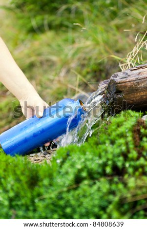 Woman filling water bottle from stream on hiking trip, summer activity