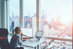 Woman financial specialist work with panoramic Manhattan view.Female economist sitting in skyscraper office interior front computer with graphs statistics of stock exchange. Earnings on raising quotes