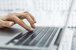 Woman finger presses a button on a laptop keyboard, business and technology concept. Close up