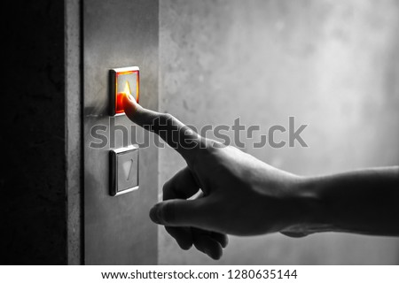 woman finger presses the elevator up button upper high level floor.