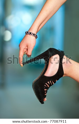 woman finger touching shoe high heel