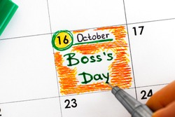 Woman fingers with pen writing reminder Boss`s Day in calendar. Close-up.