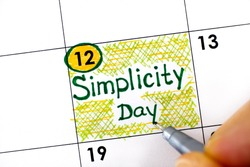 Woman fingers with pen writing reminder Simplicity Day in calendar. July 12