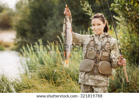 woman Fisherman on the autumn forest background.