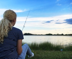 Woman fishing by a lake or a river. Sitting and waiting for the fish to bite the bait. Girl with a fishing rod fishing on the lake on a summer evening. Alone time concept.