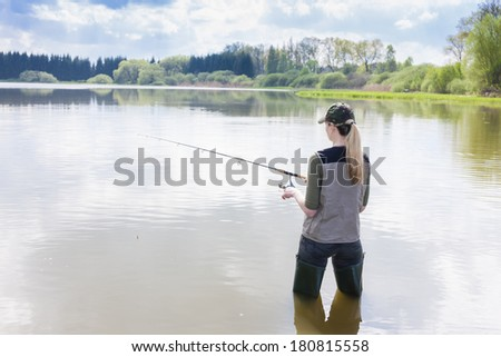 woman fishing in pond in spring