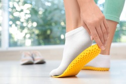 Woman fitting orthopedic insole indoors, closeup. Foot care