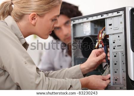 Woman fixing a computer hard drive