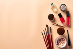 Woman flat lay makeup background with cosmetics on coral background. makeup brushes, blush balls, liquid eyeliner, lipstick, nail polish, eye shadow, perfume. space for text