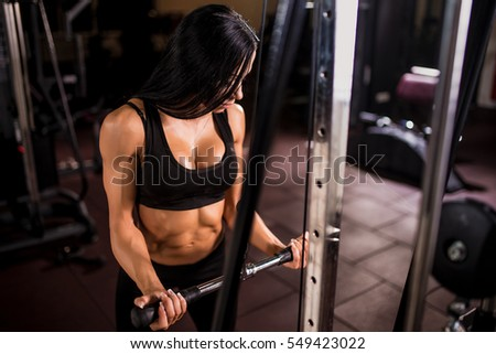 woman flexing muscles on cable machine in gym