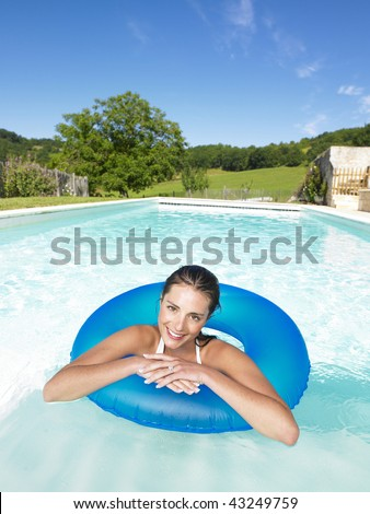 Woman floating in inner tube in pool and smiling at the camera. Vertical