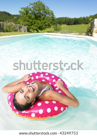 Woman floating in pink polka dot inner tube and laughing. Vertical.