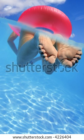 Woman floating in rubber ring in blue swimming pool