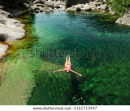 Woman floating in the clear water of a mountain river, mountain river