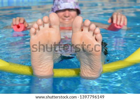 Woman floating on pool noodles in a swimming pool, feet up. Creative concept, summer holidays, leisure and relaxation
