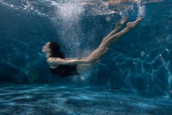 Woman floats under water in the pool, around her vials of air and spot of light.