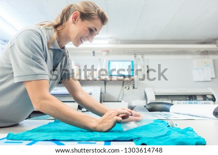Woman flock printing a T-shirt as promotional item in workshop