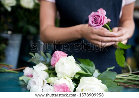 Woman florist creating a bouquet of pink and white roses