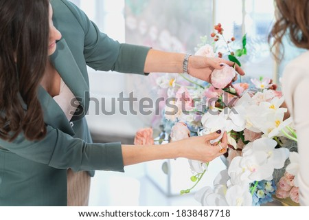 Woman florist on wedding makes flower composition for bride and groom from roses, tulips, peonies, orchids on table. Decorators working at event: birthday, anniversary, party. Hand with floral tattoo. Foto stock ©