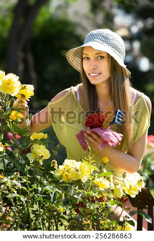 Woman florist working in the garden with blooming roses