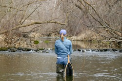 Woman fly-fishing in a Wisconsin river, early spring, catch & release.