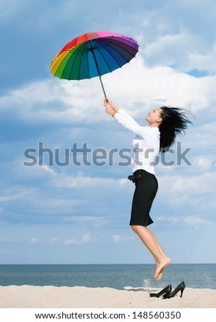 Woman flying away from her business problems with a colorful umbrella