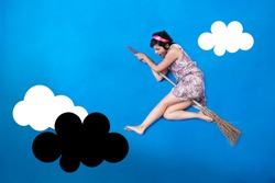 Woman flying with a broom on a blue sky attacking a black cloud