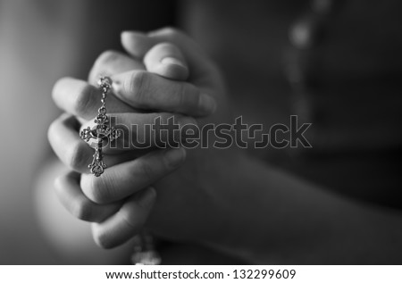 Woman folding hands and praying to God.