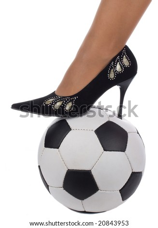 woman foot in high-heeled shoe stand on soccer ball