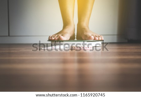 Woman foot standing on weigh scales with tape measure in foreground