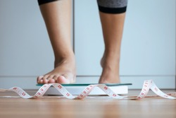 Woman foot stepping on weigh scales with tape measure in foreground,Body and good health concept,Weight loss self-efficacy